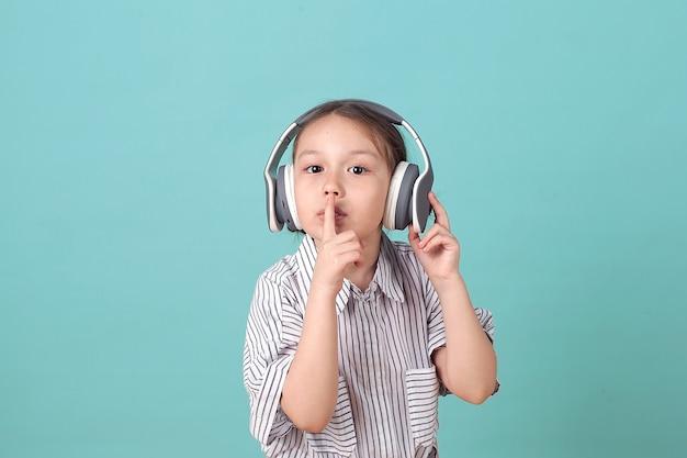 Een gelukkig klein meisje luistert naar muziek, staande op een blauwe achtergrond in de studio.