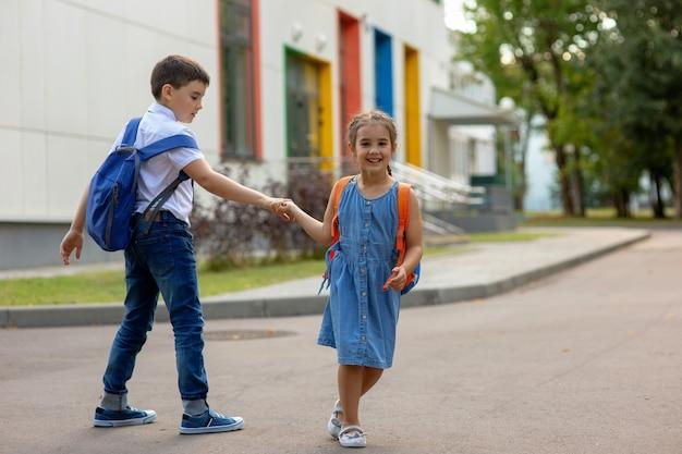 Een gelukkig klein meisje met een oranje rugzak en een broer met blauwe rugzakken houden elkaars hand vast, spelen en hebben plezier in de buurt van het schoolgebouw op een zonnige dag in de vroege herfst. kopieer ruimte