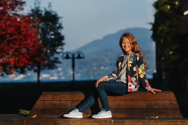 Een gelukkig klein meisje zit op een bankje in een zonnige herfstzonsondergang in de oude binnenstad van oostenrijk. een meisje poseert in een stad tegen de achtergrond van de oostenrijkse alpen. europa.velden am worther see