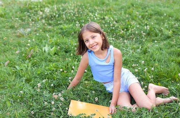 Een gelukkig klein meisje zit op het groene gras met een boek op een zomerdag. openluchtrecreatie. hij lacht en kijkt naar de camera.