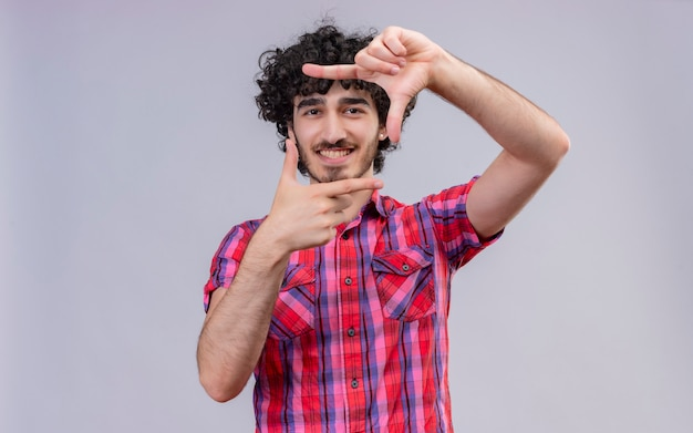Een gelukkig knappe man met krullend haar in geruit overhemd frame met handen en vingers maken