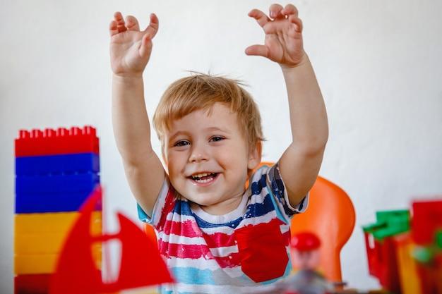 Een gelukkig lachend jongetje zit aan zijn tafel tussen het kleurrijke speelgoed met zijn handen omhoog. hoge kwaliteit foto