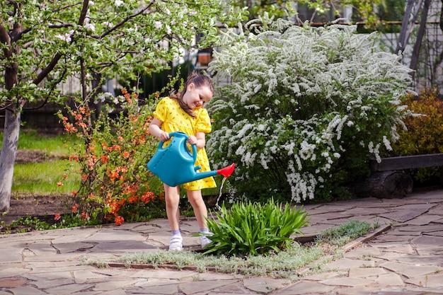 Een gelukkig lachend meisje in een gele jurk geeft bloemen water uit een blauwe gieter, een jonge tuinier...