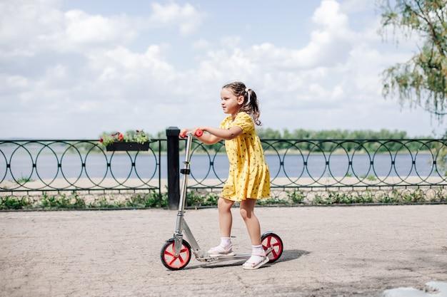 Een gelukkig lachend meisje in een jurk rijdt op een scooter langs de rivieroever in de stad een meisje leert...