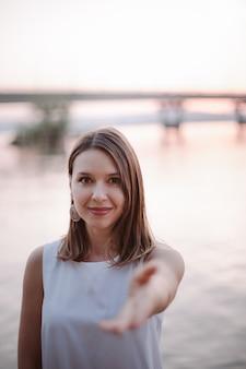 Een gelukkig lachende blanke vrouw strekt haar hand uit naar de camera en biedt aan om op een date te gaan of...