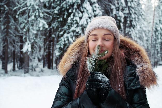 Een gelukkig lachende vrouw in warme kleren houdt een dennentakje in haar hand en inhaleert de geur van dennennaalden. prachtig dennenbos onder de sneeuw, ijzige winter.