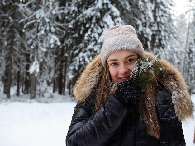 Een gelukkig lachende vrouw in warme kleren houdt een naaldtakje in haar hand