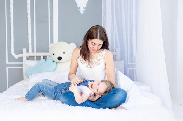 Een gelukkig, liefdevol gezin. moeder en zoontje spelen thuis op bed, hebben plezier en lachen.