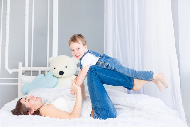 Een gelukkig, liefdevol gezin. moeder en zoontje spelen thuis op het bed, hebben plezier en lachen