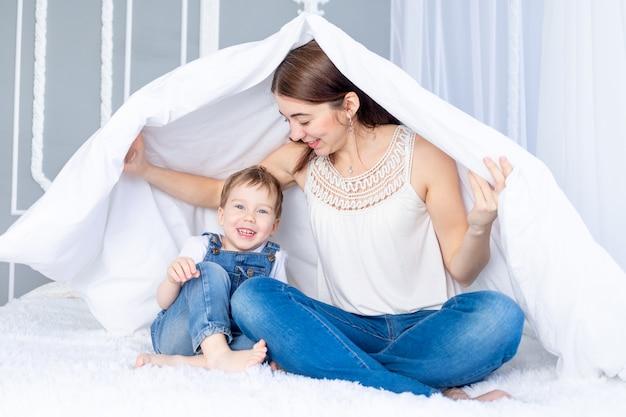 Een gelukkig, liefdevol gezin. moeder en zoontje spelen thuis op het bed onder de deken