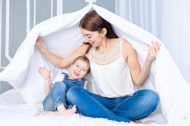 Een gelukkig, liefdevol gezin. moeder en zoontje spelen thuis op het bed onder de deken.