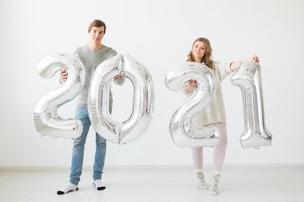 Een gelukkig liefdevol stel houdt zilveren 2021-ballonnen vast