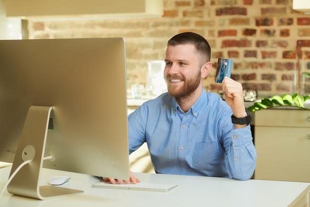 Een gelukkig man met een baard zit achter de computer en het kiezen van producten in een online winkel thuis