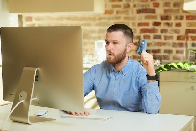 Een gelukkig man met een baard zit achter de computer verrast door de prijzen op een online winkel thuis