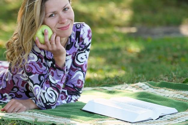 Een gelukkig meisje dat een boek leest, de bijbel met appel
