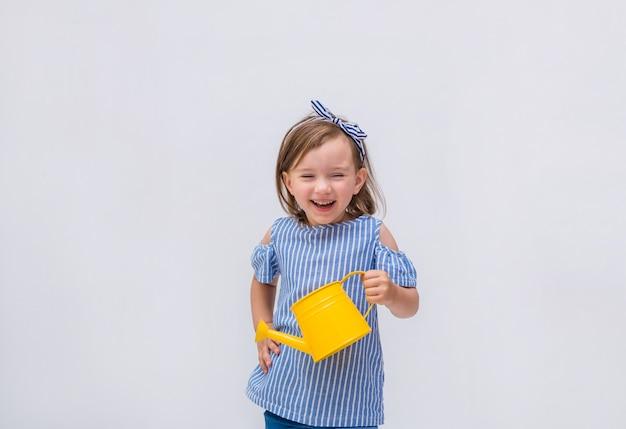 Een gelukkig meisje houdt een gieter en lacht op een geïsoleerd wit