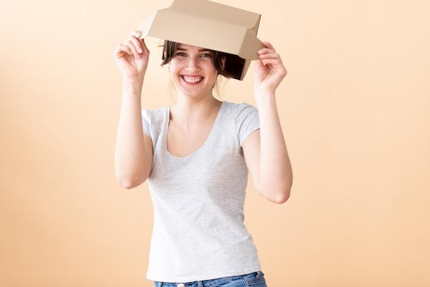Een gelukkig meisje in een grijs t-shirt zette een doos op haar hoofd. heb een goed humeur en geniet van het leven