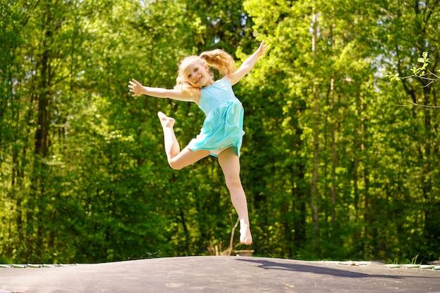 Een gelukkig meisje in een jurk springt op een trampoline in een park op een zonnige zomerdag
