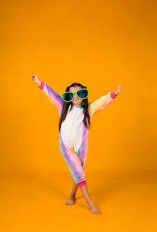 Een gelukkig meisje in een pluche jumpsuit en grote bril toont haar handen op een gele achtergrond met een plek voor tekst