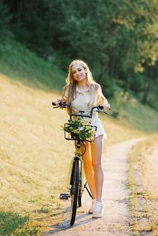 Een gelukkig meisje in een witte korte broek en een beige shirt met gele bloemen in een fietsmand. de zon op de achtergrond