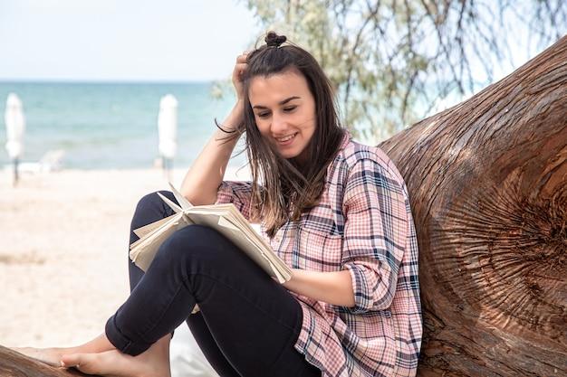 Een gelukkig meisje leest een boek over een boom. de persoon abstraheerde van alles. het concept van ontspanning en rust.