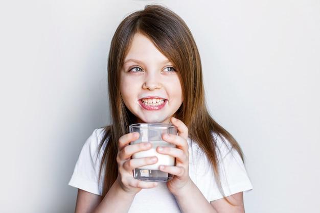 Een gelukkig meisje met een glas melk die vrolijk lacht met melk op haar lippen