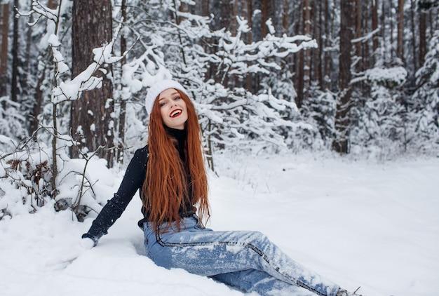 Een gelukkig meisje met fel rood haar zit in de sneeuw in een besneeuwd bos. een vrouw geniet van het goede winterweer.