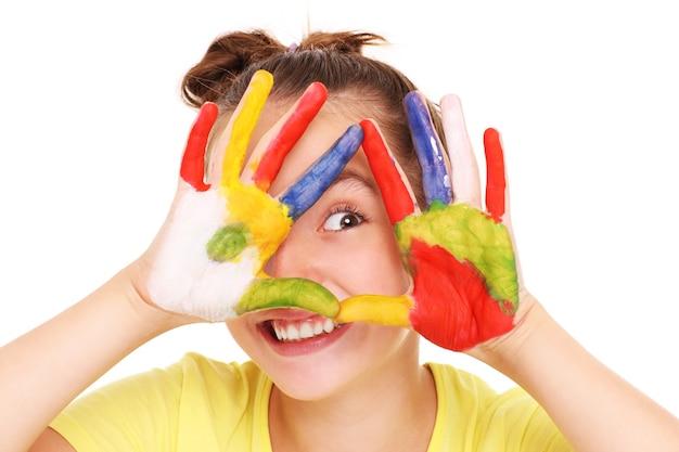 Een gelukkig meisje met geschilderde handen op een witte achtergrond