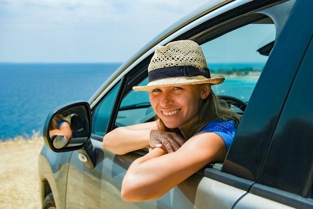 Een gelukkig meisje uit auto op zee