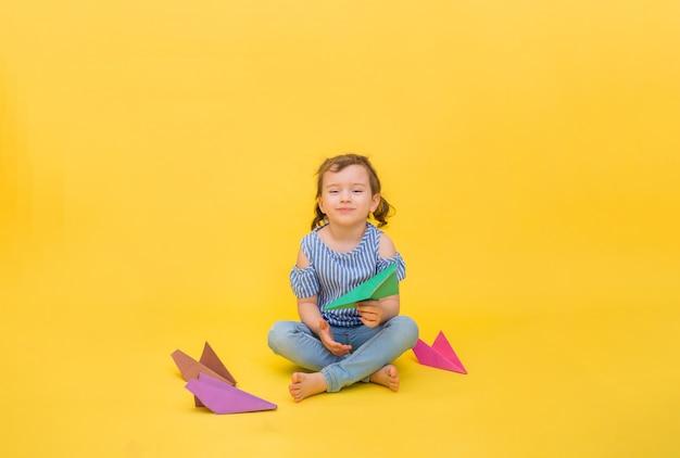 Een gelukkig meisje zit met origamidocument vliegtuigen op geel