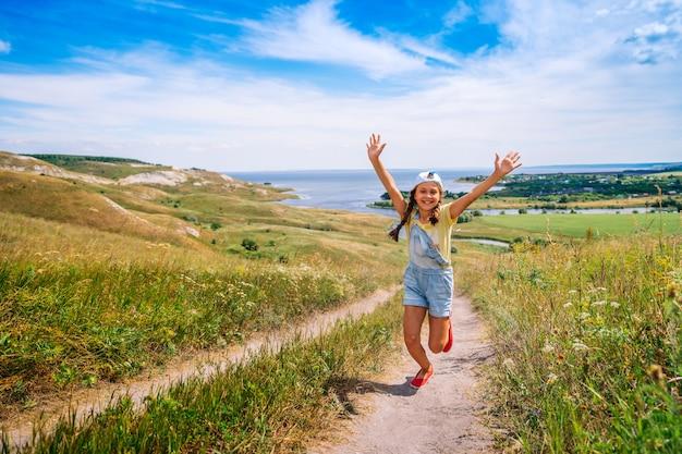 Een gelukkig meisjeskind in een jumpsuit van denim loopt met haar handen open tegen van een schilderachtig landschap