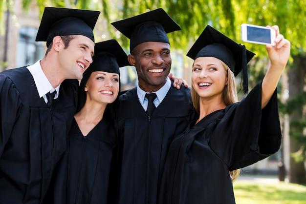 Een gelukkig moment vastleggen. vier afgestudeerden in afstudeerjurken die dicht bij elkaar staan en selfie maken