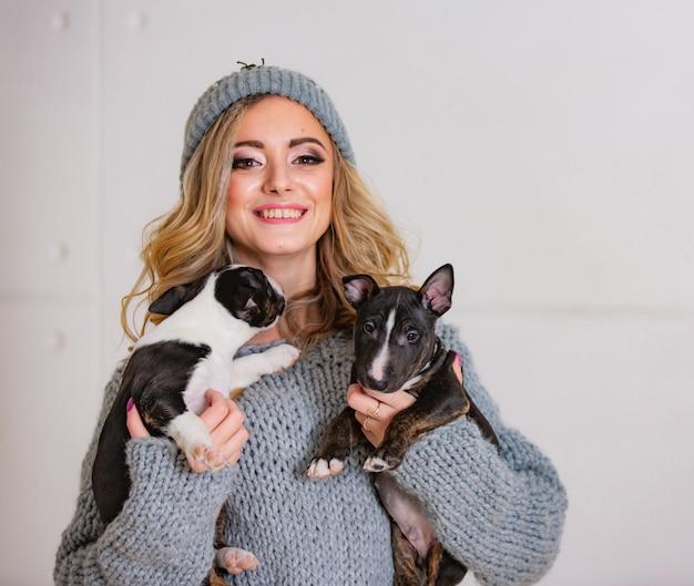 Een gelukkig mooi meisje dat kleine puppy koestert