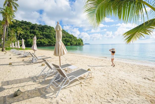 Een gelukkig mooie vrouw in gele bikini genieten en ontspannen op het strand, zomer en vakantie concept