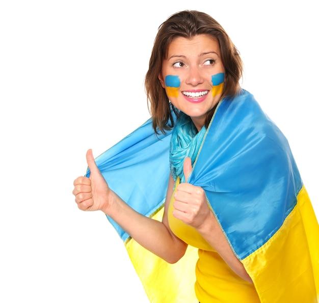 Een gelukkig oekraïens meisje met de vlag die tegen witte achtergrond glimlacht