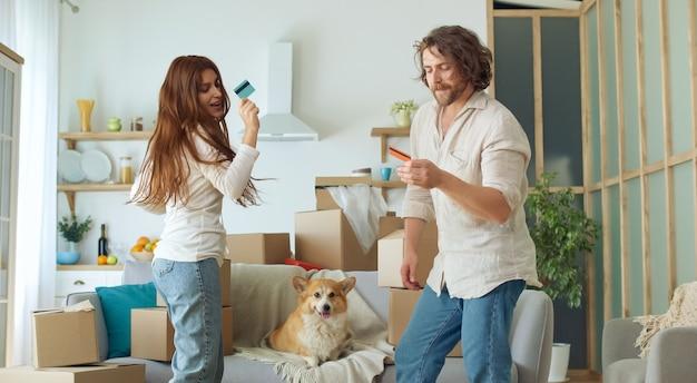 Een gelukkig paar dat viert, danst en plezier heeft in de woonkamer met dozen. jonge man met borstelharen en langharige vrouw die lacht en lacht. mooi koppel dat samen plezier heeft tijdens het dansen.