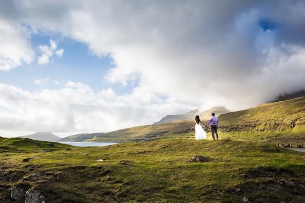 Een gelukkig paar in trouwjurken of de bruid en bruidegom hand in hand en kijken naar de natuur. faeröer