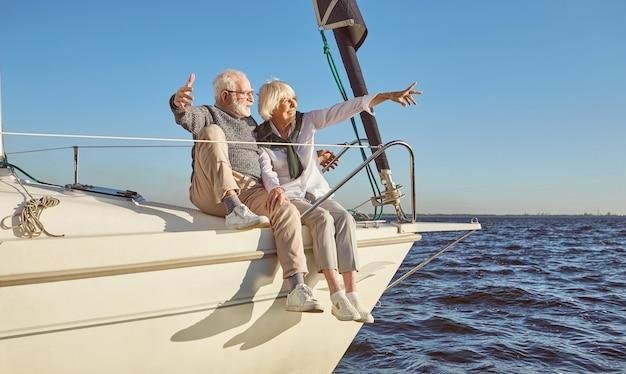 Een gelukkig senior koppel zittend aan de zijkant van een zeilboot op een kalme blauwe zee wijzend op landschap