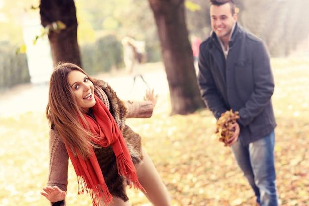 Een gelukkig stel dat plezier heeft in het park in de herfst