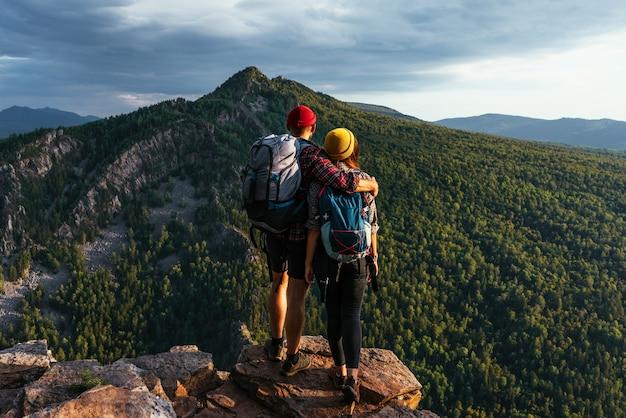 Een gelukkig stel in de bergen bewondert de prachtige uitzichten. een man en een vrouw met rugzakken op de berg bewonderen het panoramische uitzicht. reizigers genieten van het beklimmen van de berg bij zonsondergang. ruimte kopiëren