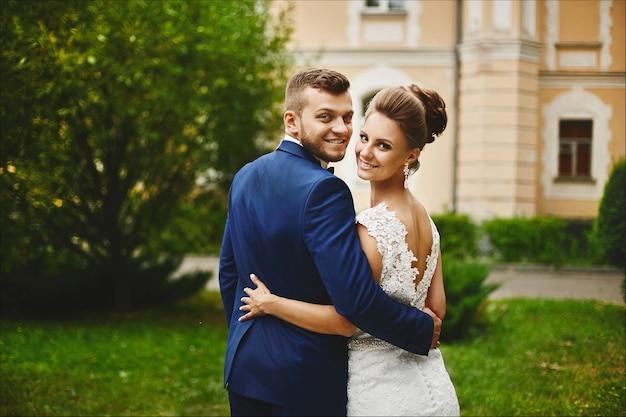Een gelukkig stel jonggehuwden knuffelen na de huwelijksceremonie buiten, mooi modelmeisje