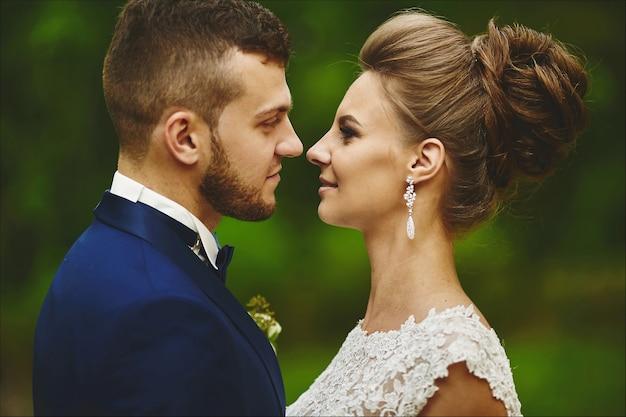 Een gelukkig stel pasgetrouwden die elkaar in de ogen kijken tijdens de huwelijksceremonie buiten