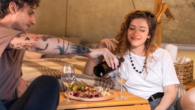 Een gelukkig stel rust in een tent bij glamping wine and food