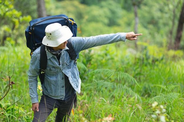 Een gelukkig wandelende man loopt door het bos met een rugzak.