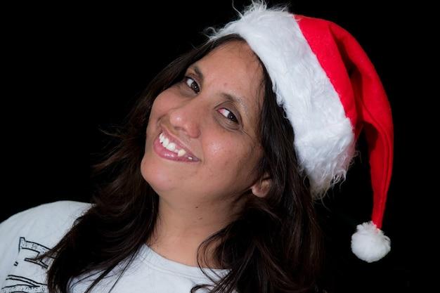 Een gelukkige aantrekkelijke glimlachende dame in kerstmuts, vrolijk kijkend naar de camera