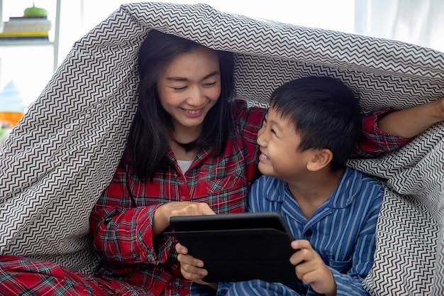 Een gelukkige aziatische familiemoeder en een zoon doen activiteit samen in woonkamer speelspel op digitale tablet.