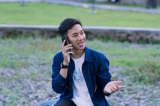 Een gelukkige aziatische jonge man zit in een park en iets uit te leggen aan zijn collega aan de telefoon
