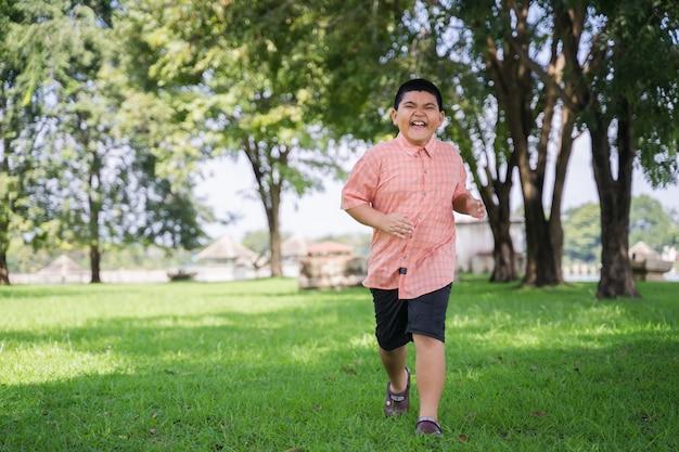 Een gelukkige aziatische jongen die in het park openlucht in vakantie loopt