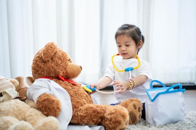 Een gelukkige aziatische meisjes spelen arts of verpleegster die een stethoscoop aan stuk speelgoed luisteren.