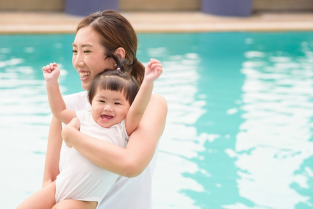 Een gelukkige aziatische moeder en dochter genieten van zwemmen in het zwembad